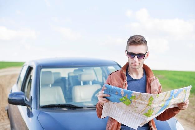 Jonge man leest wegenkaart in de buurt van zijn auto