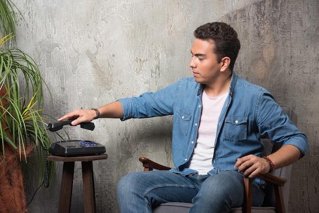 Jonge man legde de telefoon neer en zat op een stoel. hoge kwaliteit foto
