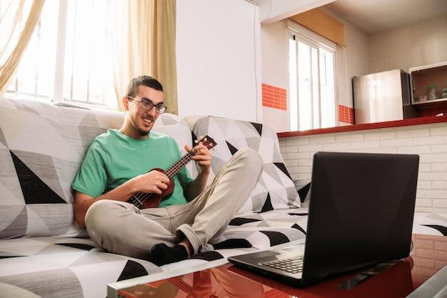 Jonge man leren om de ukelele online te spelen vanaf zijn bank