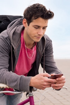 Jonge man leunend op een fiets met behulp van slimme telefoon