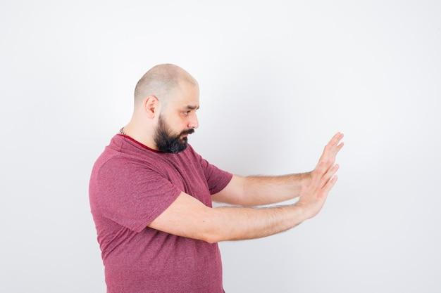 Jonge man leunend tegen muur met handen in roze t-shirt.