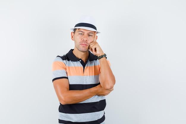 Jonge man leunend wang op opgeheven hand in t-shirt en hoed en kijkt attent