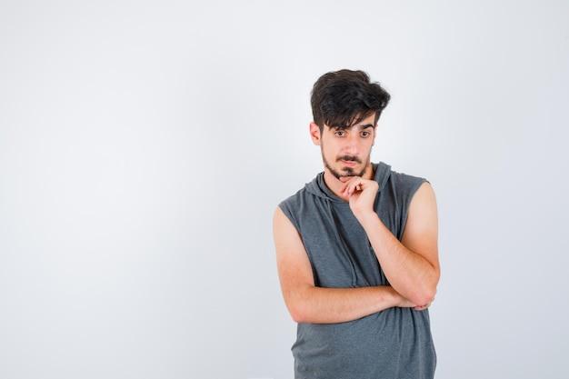 Jonge man leunt wang op palm in grijs t-shirt en kijkt peinzend