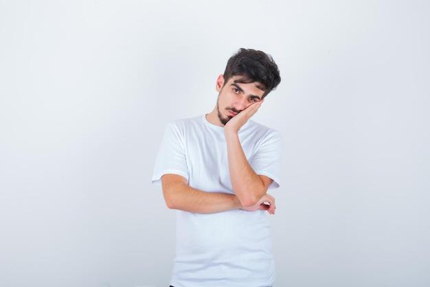 Jonge man leunt wang op palm in wit t-shirt en ziet er moe uit