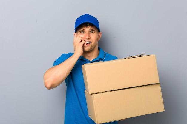 Jonge man levert pakketten bijten vingernagels, nerveus en erg angstig.