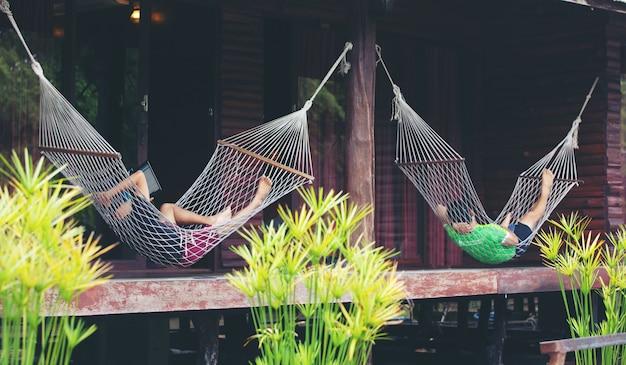 Jonge man liggend in witte hangmat in het resort en luisteren naar muziek op smartphone.