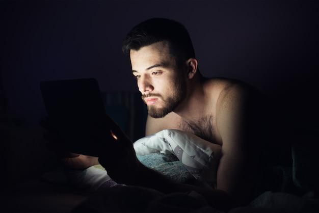 Jonge man liggend op bed op zijn buik en kijk naar het scherm van de tablet. geconcentreerde kalme man die spelletjes speelt of zich vermaakt. donker 's nachts.