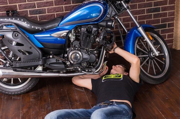 Jonge man liggend op de houten vloer terwijl hij zijn blauwe sportmotor thuis repareert.
