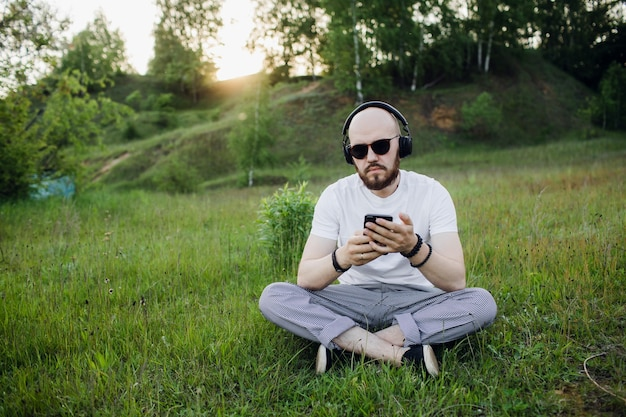 Jonge man liggend op gras en muziek luisteren van hoge kwaliteit foto