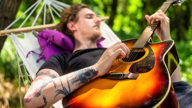 Jonge man liggend op hangmat speelt gitaar. groen rondom. glamping