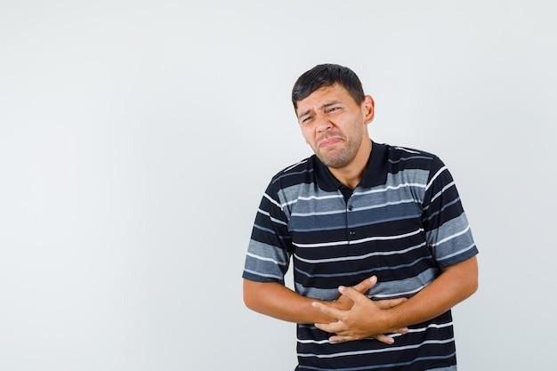 Jonge man lijdt aan buikpijn in t-shirt en ziet er bedroefd uit. vooraanzicht.