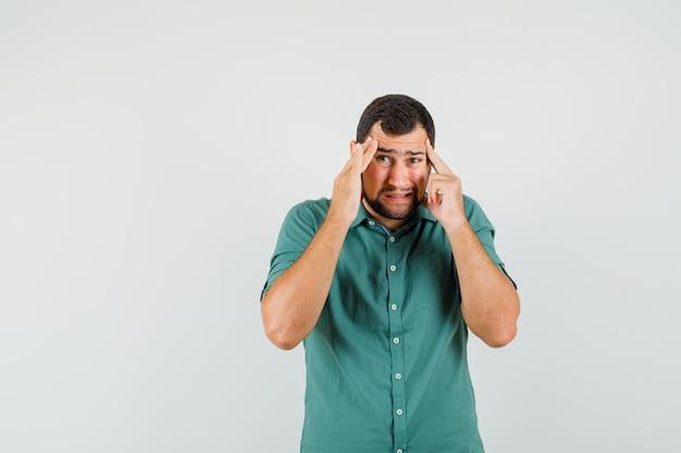 Jonge man lijdt aan hoofdpijn in groen shirt en ziet er ongemakkelijk uit, vooraanzicht.