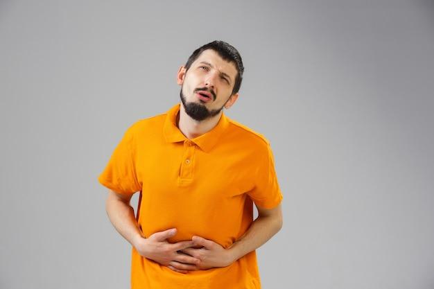 Jonge man lijdt aan pijn voelt zich ziek ziek en zwakte isolted op muur