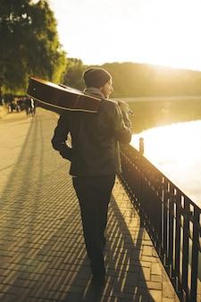 Jonge man loopt door het meer en houdt gitaar