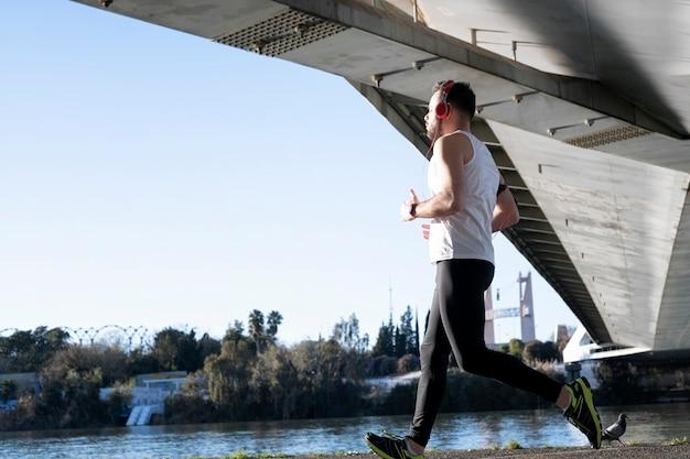Jonge man loopt in een wit overhemd over een brug. hij luistert naar muziek en hij heeft een paar helmen op.