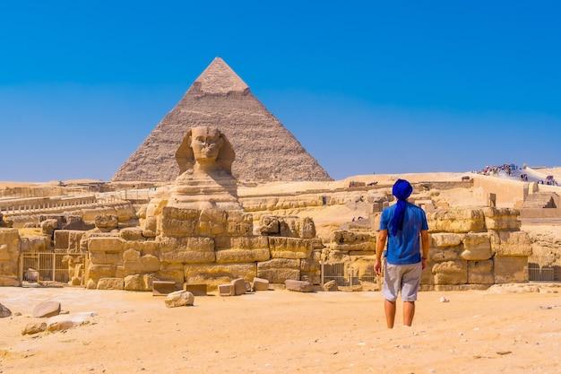 Jonge man loopt naar de grote sfinx van gizeh a