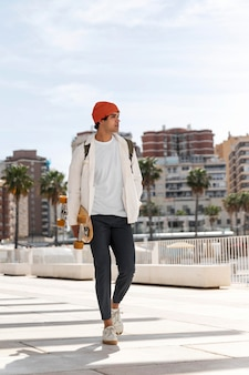 Jonge man lopen terwijl hij zijn skateboard vasthoudt