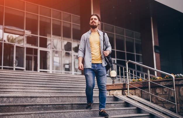 Jonge man lopen trappen van universiteitsgebouw