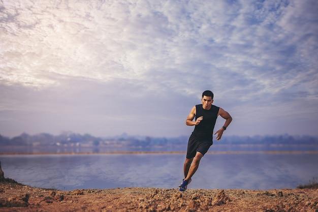 Jonge man loper loopt parcours op zonsopgang aan het meer gezond en lifestyle concept