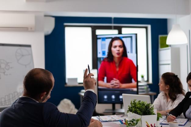 Jonge man luisteren coach tijdens online videogesprek in vergaderruimte
