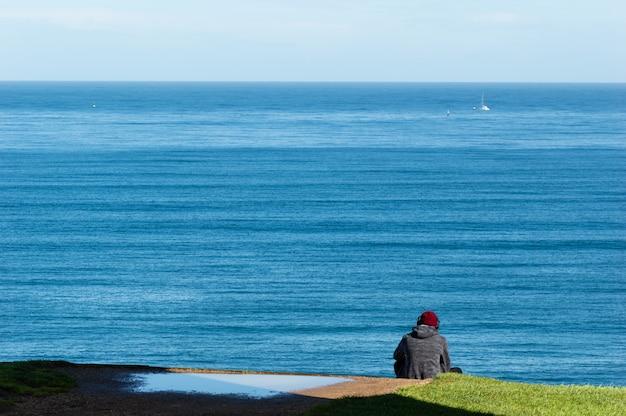 Jonge man luisteren muziek zit op de rand van de klif van de zee.