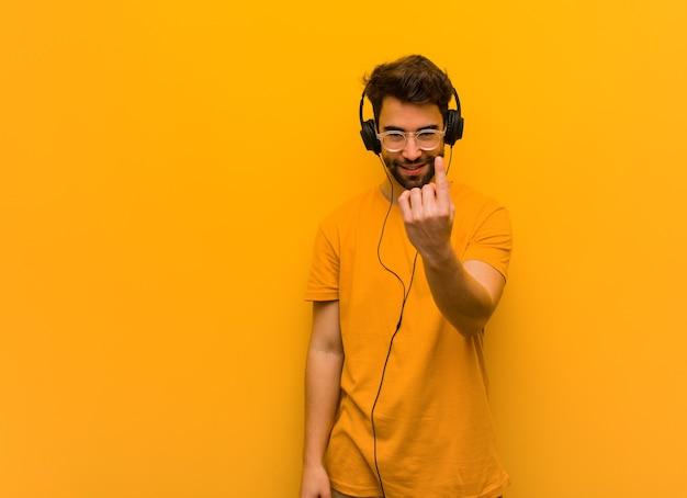 Jonge man luisteren naar muziek die uitnodigt om te komen