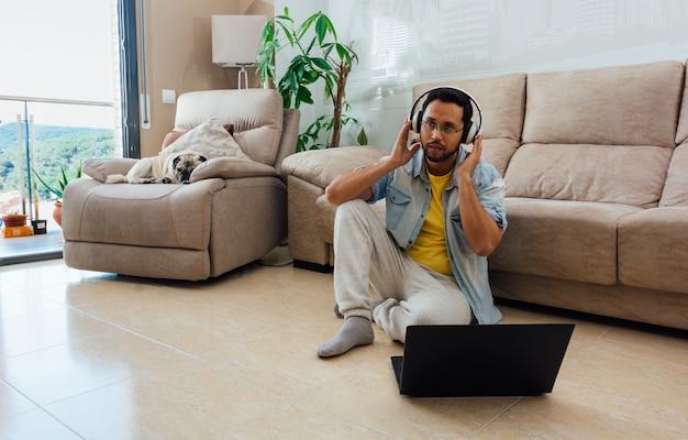 Jonge man, luisteren naar muziek met een koptelefoon en met behulp van een laptop om vanuit huis te werken