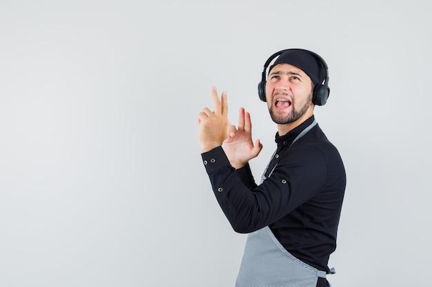 Jonge man luisteren naar muziek met een koptelefoon in shirt, schort en op zoek geamuseerd.