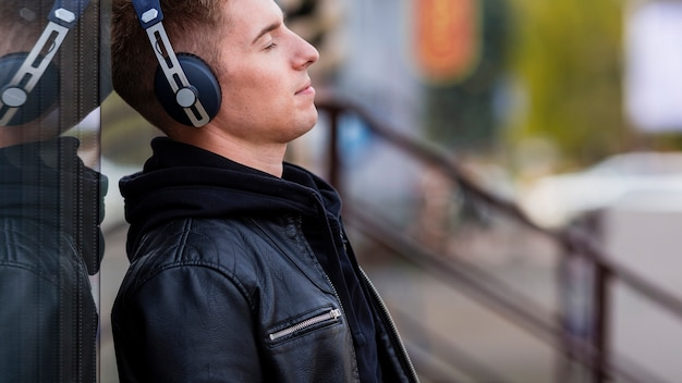 Jonge man luisteren naar muziek op koptelefoon met kopie ruimte