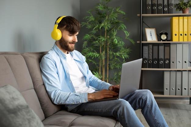 Jonge man luisteren naar muziek op koptelefoon tijdens het werken