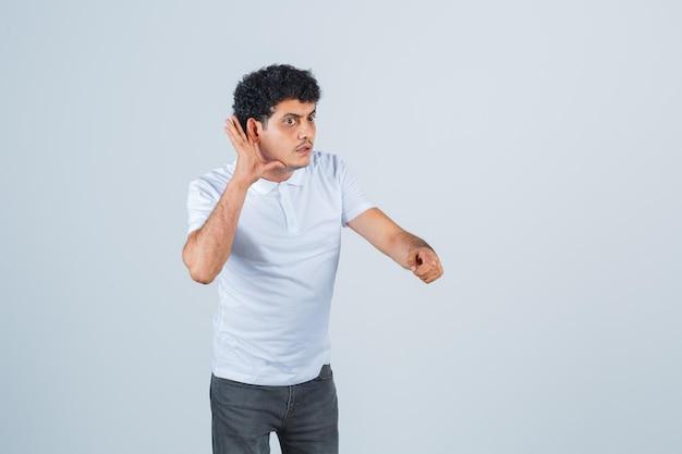 Jonge man luistert privégesprek af, wijst naar camera in wit t-shirt, broek en kijkt geschokt, vooraanzicht.