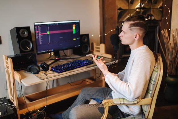 Jonge man maakt een podcast audio-opname thuis man met behulp van pc en twee professionele microfoons