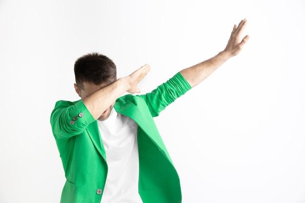 Jonge man maakt een scharbeweging met zijn armen op een grijze achtergrond. menselijke emoties, gezichtsuitdrukking concept