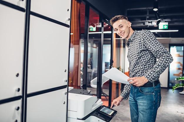 Jonge man maakt kopieën van documenten