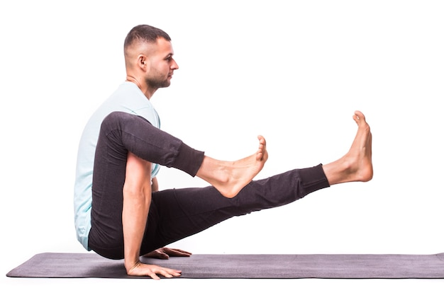 Jonge man maakt yoga geïsoleerd op witte achtergrond