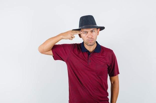 Jonge man maakt zelfmoordgebaar in t-shirt, hoed en ziet er depressief uit. vooraanzicht.
