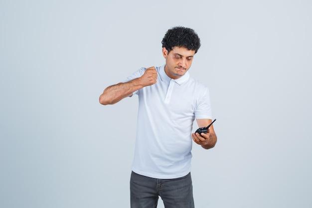Jonge man maakt zich klaar om te slaan op een walkietalkie-telefoon in wit t-shirt, broek en ziet er geïrriteerd uit, vooraanzicht.