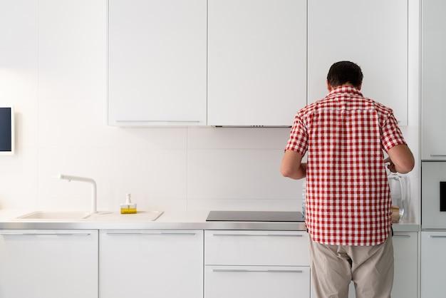 Jonge man makind thee staande naast de open koelkast.