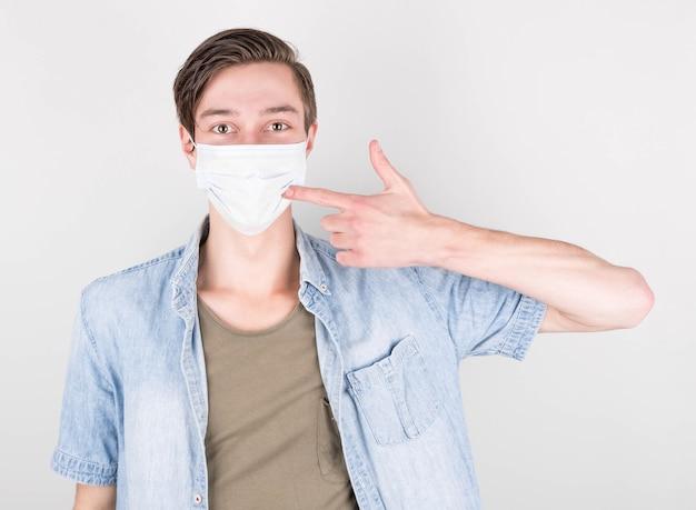 Jonge man man in denim t-shirt poseren geïsoleerd op witte muur achtergrond studio portret. mensen emoties levensstijl concept. kopieer ruimte voor kopiëren. wijzende wijsvinger op een medisch masker