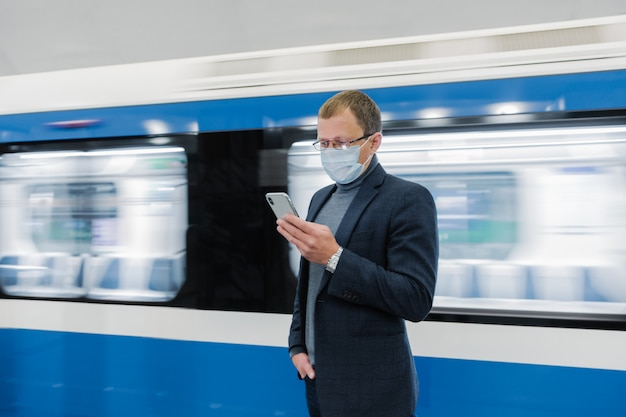 Jonge man manager gebruikt mobiel, voorkomt verspreiding van coronavirus, poseert tegen metro, poseert op platform, controleert nieuws online, draagt medisch masker. epidemische situatie, concept van de gezondheidszorg