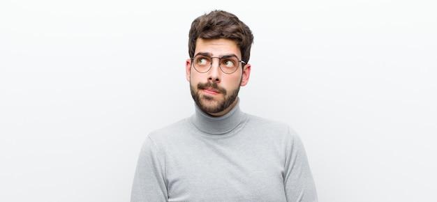 Jonge man manager met verbaasd, nerveus, bezorgd of bang blik, op zoek naar de kant naar kopie ruimte tegen witte muur