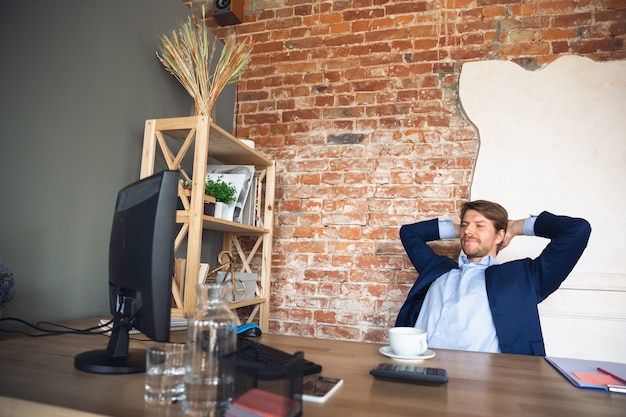 Jonge man, manager, team leidde na quarantaine weer aan het werk in zijn kantoor, voelt zich gelukkig en geïnspireerd