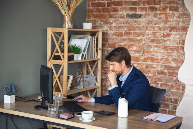 Jonge man, manager, team leidde na quarantaine weer aan het werk in zijn kantoor, voelt zich gelukkig