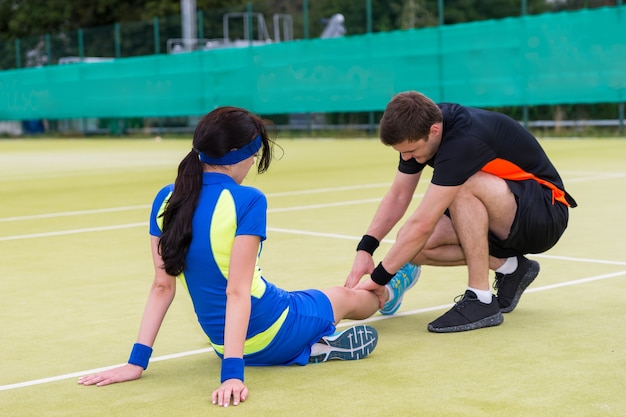 Jonge man massage aan zijn vrouwelijke tennispartner na tenniswedstrijd op een rechtbank buiten in de zomer of lente