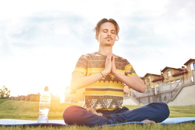 Jonge man mediteren buiten in het park, zittend met de ogen dicht en zijn handen samen.