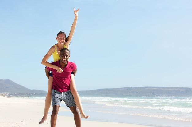 Jonge man meeliften vriendin op het strand