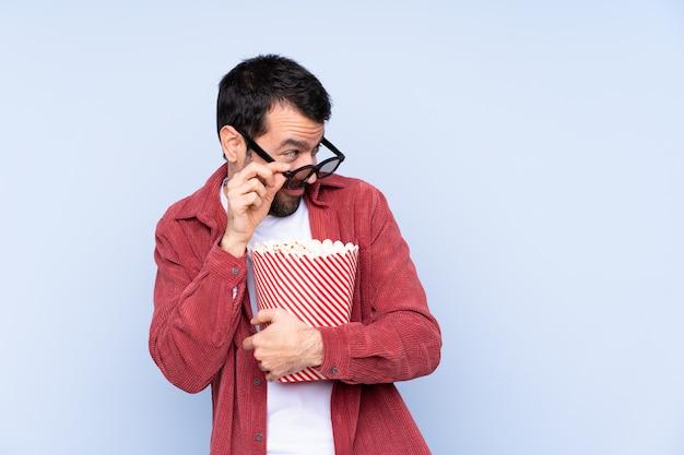 Jonge man met 3d bril en houden een grote emmer popcorns
