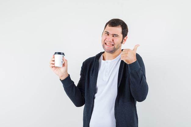 Jonge man met afhaalmaaltijden koffiekopje en duim opdagen in wit t-shirt en zwarte hoodie met ritssluiting en op zoek gelukkig. vooraanzicht.