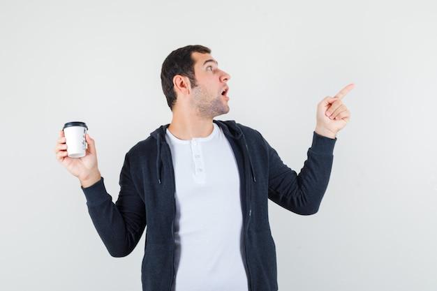 Jonge man met afhaalmaaltijden koffiekopje en naar rechts wijzend met wijsvinger in wit t-shirt en zwarte hoodie met ritssluiting en op zoek verrast, vooraanzicht.