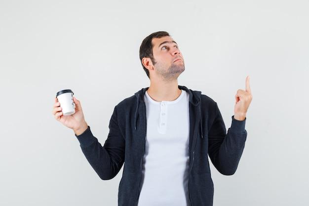 Jonge man met afhaalmaaltijden koffiekopje en omhoog met wijsvinger in wit t-shirt en zwarte hoodie met rits aan de voorkant en op zoek naar serieuze, vooraanzicht.